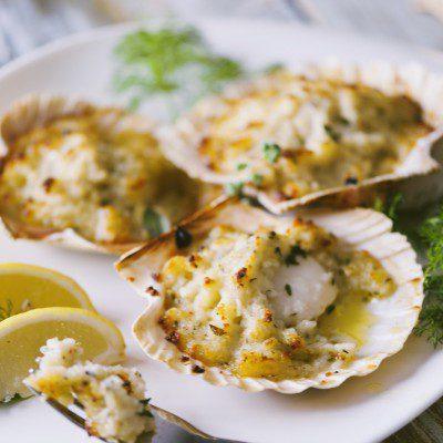 Capesante gratinate con spicchi di limone nel piatto