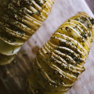 Patate hasselback a ventaglio con gli aromi pronte per essere gustate