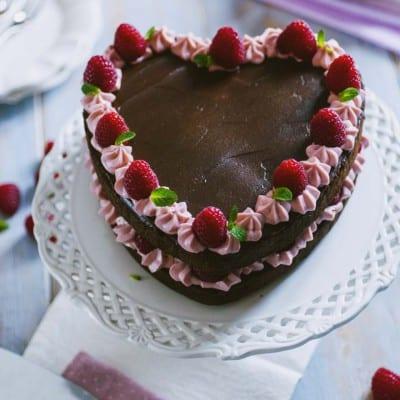Torta cuore al cioccolato e lamponi, decorata con ganache e lamponi freschi per San Valentino