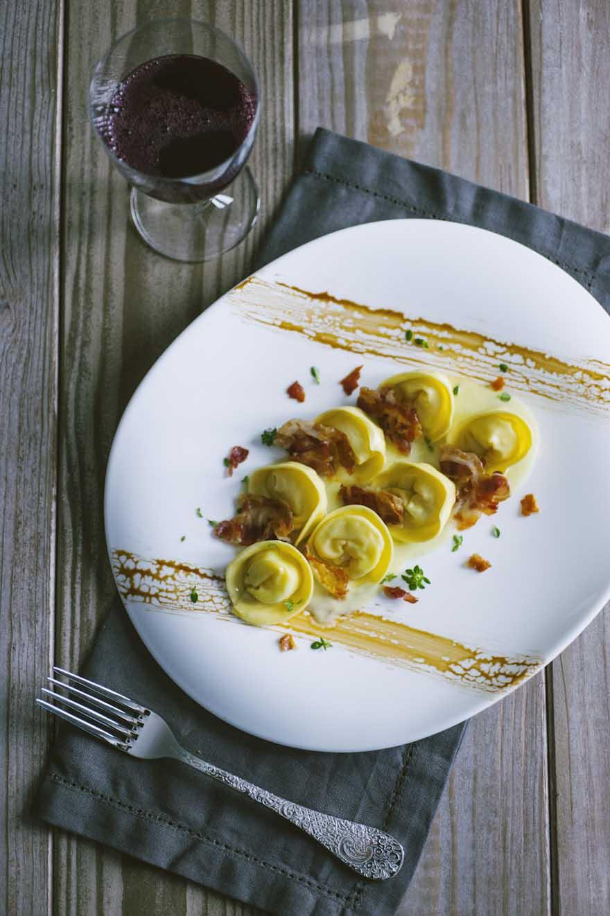 Cappellacci ripieni di patate, saporiti e disposti nel piatto