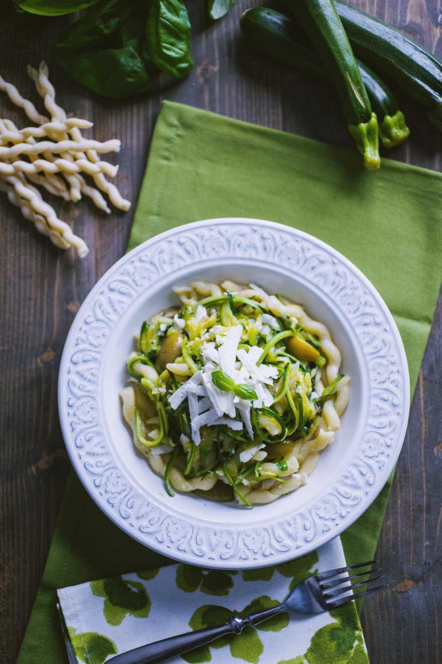 Pasta con le zucchine, servita con una grattugiata di ricotta fresca e qualche fogliolina di basilico