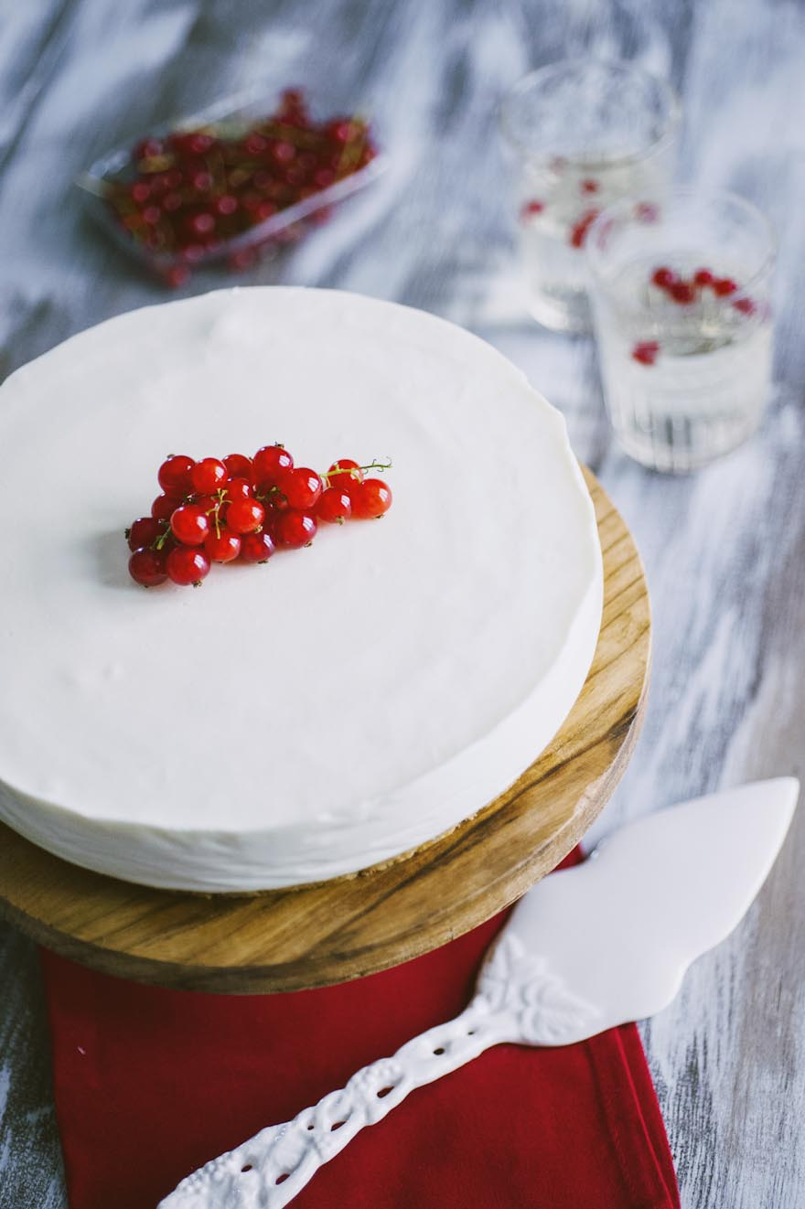 Torta fredda allo yogurt, decorata con brillanti ribes e pronta per essere assaggiata