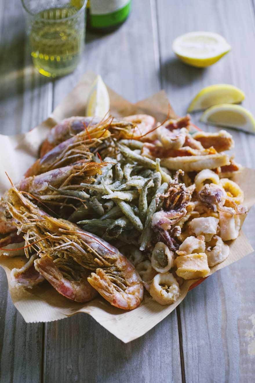 Fritto misto di pesce, servito su un vassoio con spicchi di limone