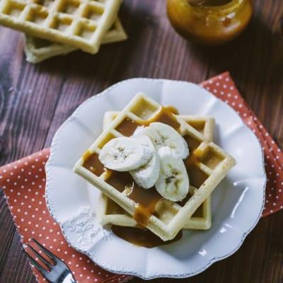Waffle senza glutine, servito con un velo di salsa al caramello e banane a fette