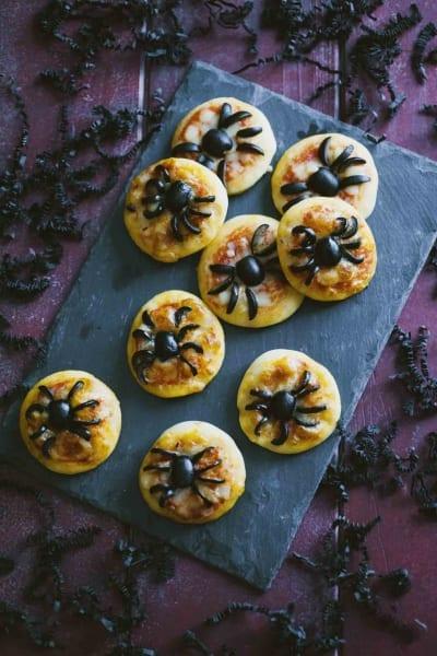 Pizzette ragno, presentate su un tetro tagliere nero
