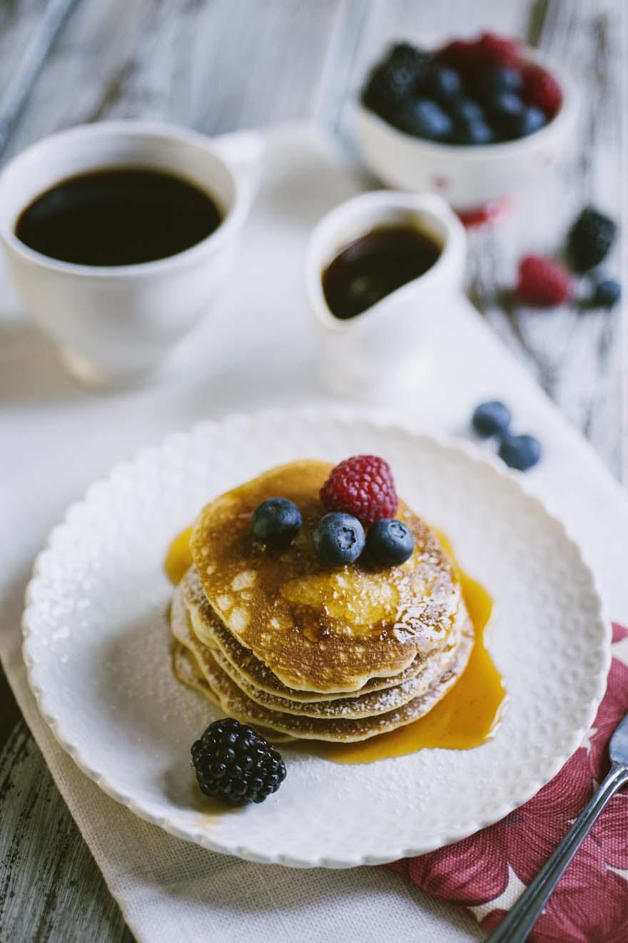 Pancakes senza glutine e latticini, guarniti con sciroppo d'acero e frutta fresca