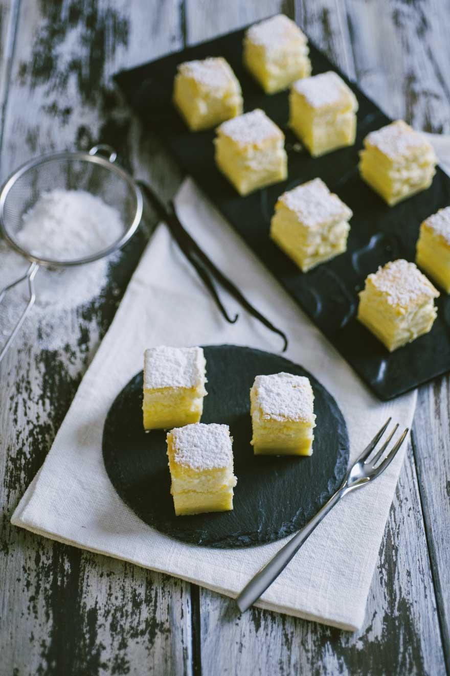 Torta magica alla vaniglia, tagliata e servita a cubotti da mangiare in un col boccone