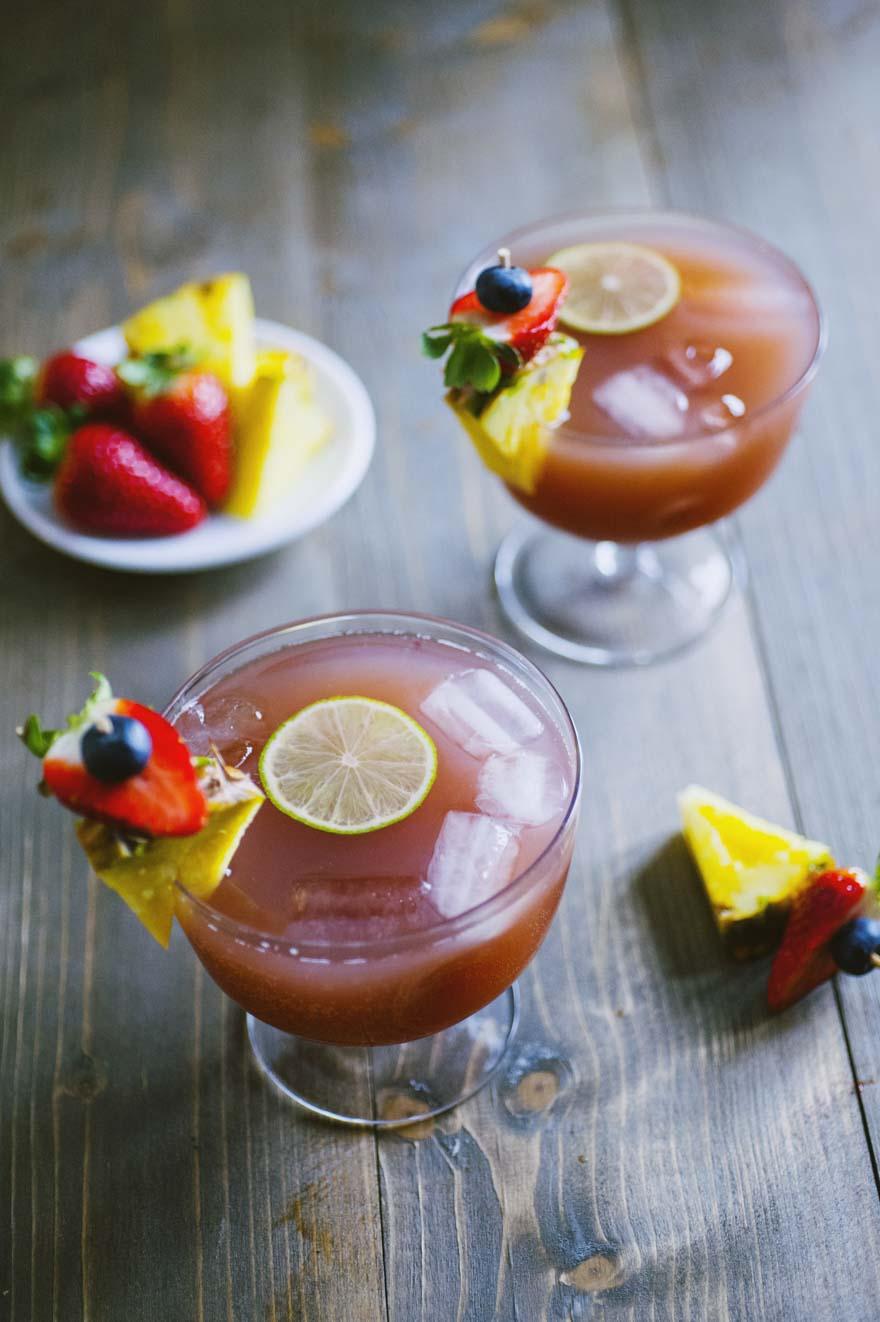 Analcolico alla frutta, servito in calice e decorato con uno spiedino di frutta fresca