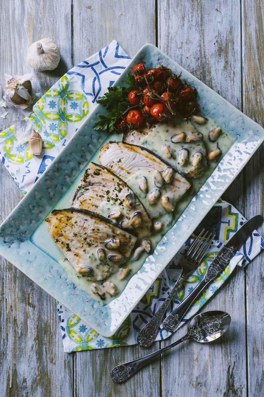 Pesce spada con crema di patate e cozze, servito con pomodorini