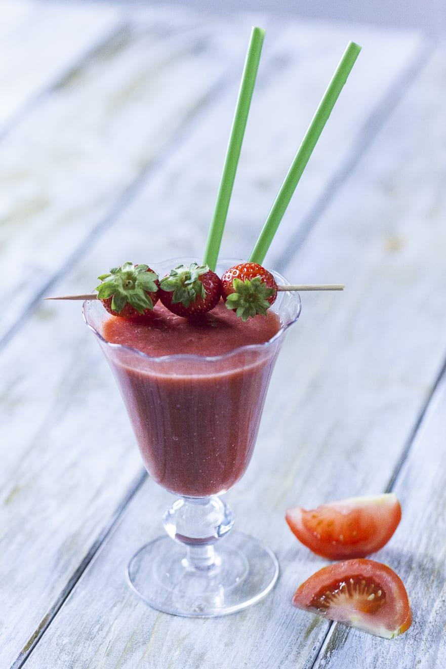 Smoothie di fragola, pomodoro e zenzero, servito con uno spiedino di fragole