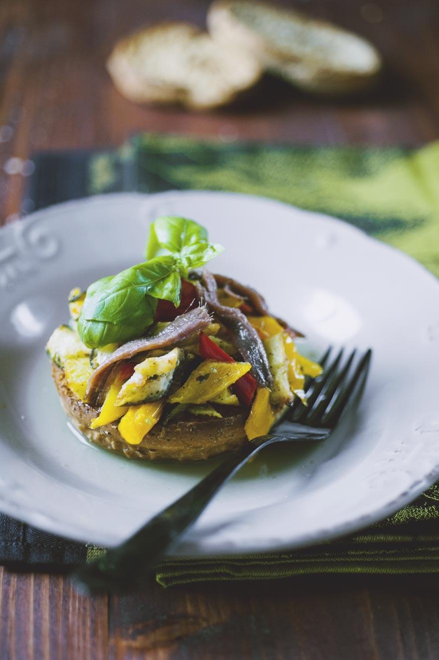 Frisella con caponata di verdure servita nel piatto e pronta all'assaggio