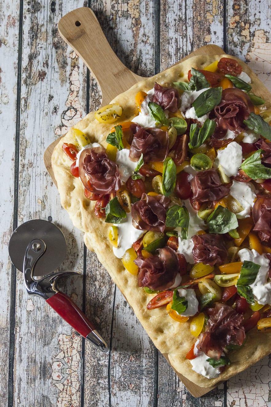 Focaccia con bresaola, pomodorini e stracciatella su tagliere