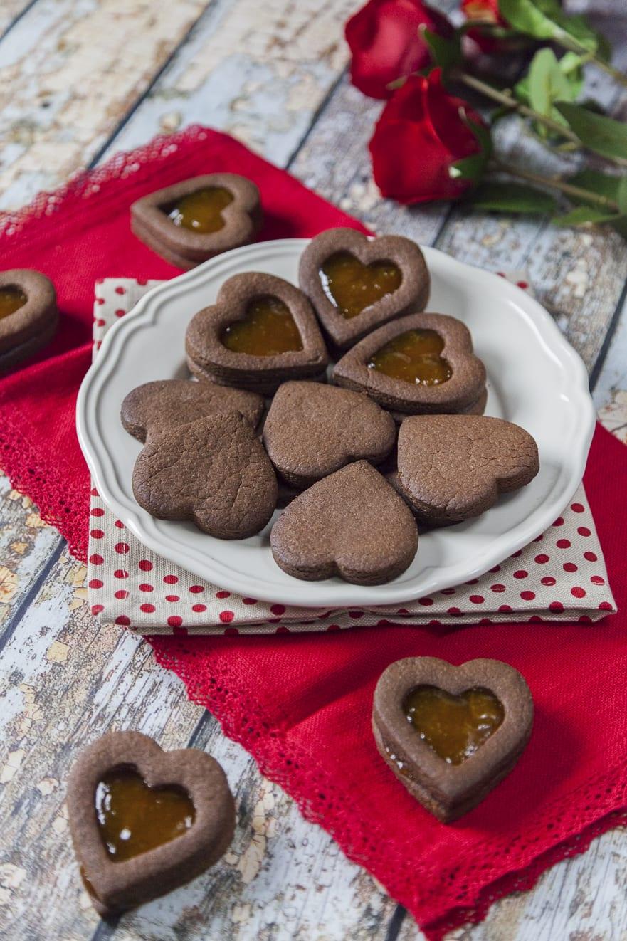 Biscotti di San Valentino al caco a forma di cuore classici e con confettura