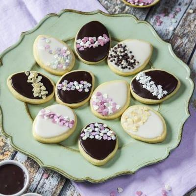Biscotti di Pasqua decorati glassati bianchi neri e rosa con zuccherini dolci e scaglie di cioccolato