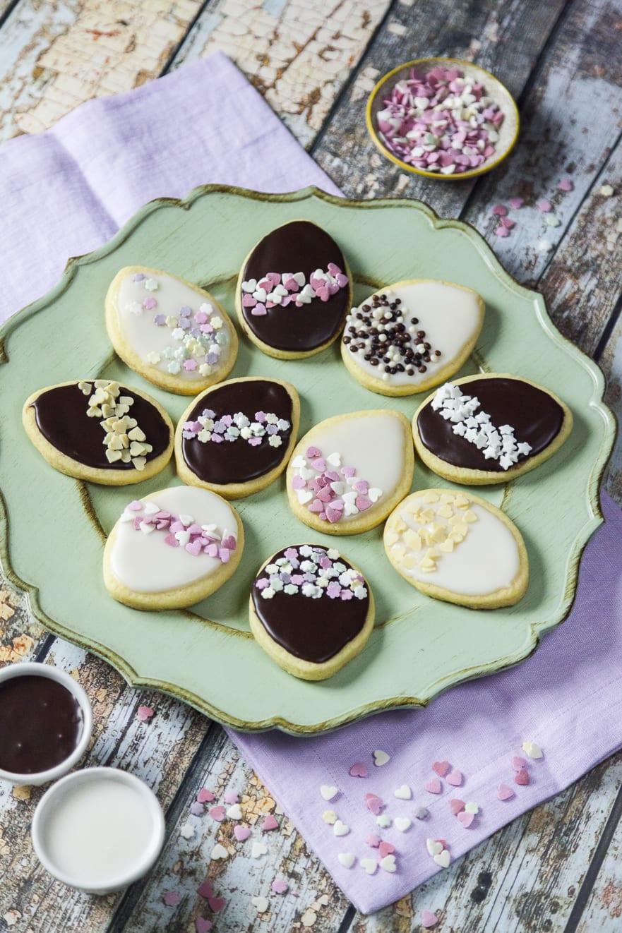 Biscotti uova di Pasqua decorati glassati bianchi neri e rosa con zuccherini dolci e scaglie di cioccolato