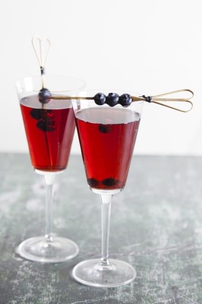 Kir cocktail, servito in calice con spiedini di mirtilli