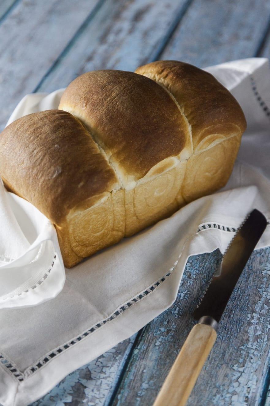 Pane giapponese morbido al forno su tovaglia bianca con coltello ricetta semplice e facile