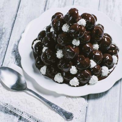 Profiteroles al cioccolato bignè ripieni di crema chantilly a piramide