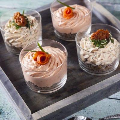 Mousse al salmone e mousse ai pomodori secchi in bicchiere pronti per essere serviti
