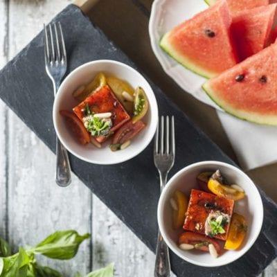 Anguria grigliata con pomodori, acciughe e basilico