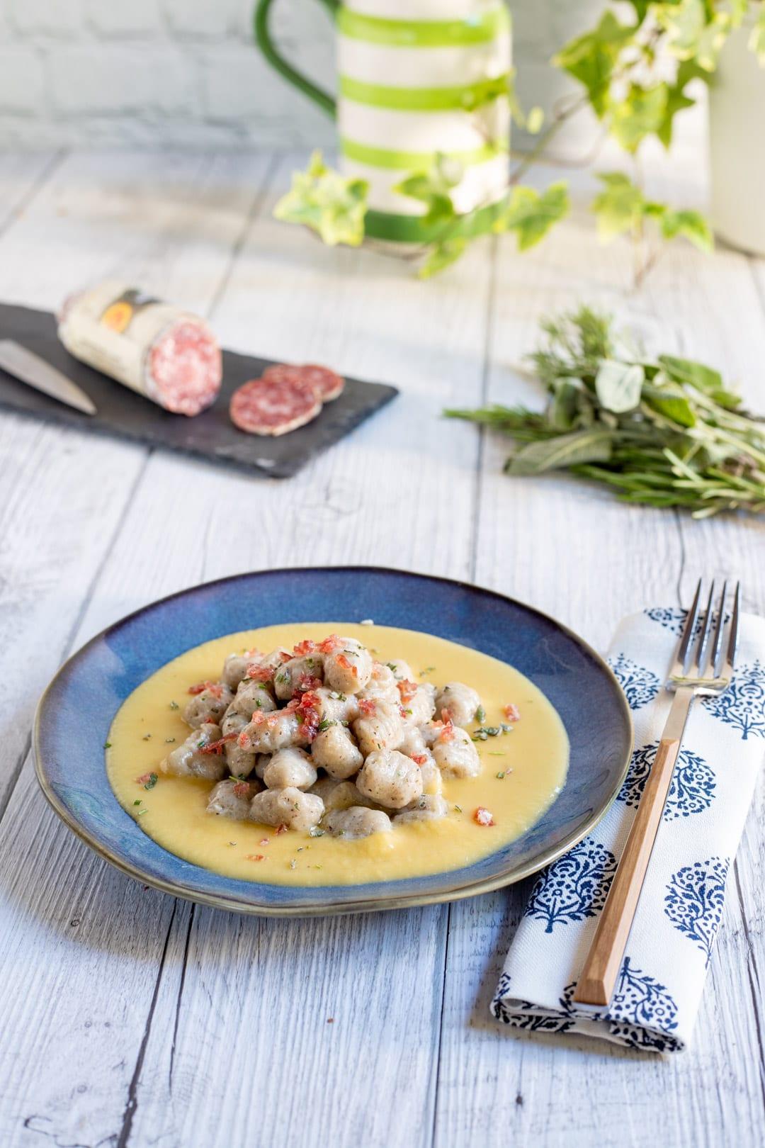 gnocchetti alle erbe con briciole di salame su crema di pane pronti per l'assaggio