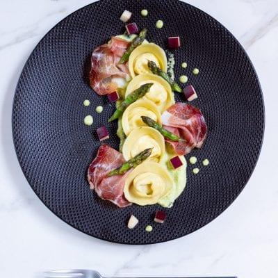 Cappellacci con ricotta, speck, mele e crema di asparagi pronto per l'assaggio