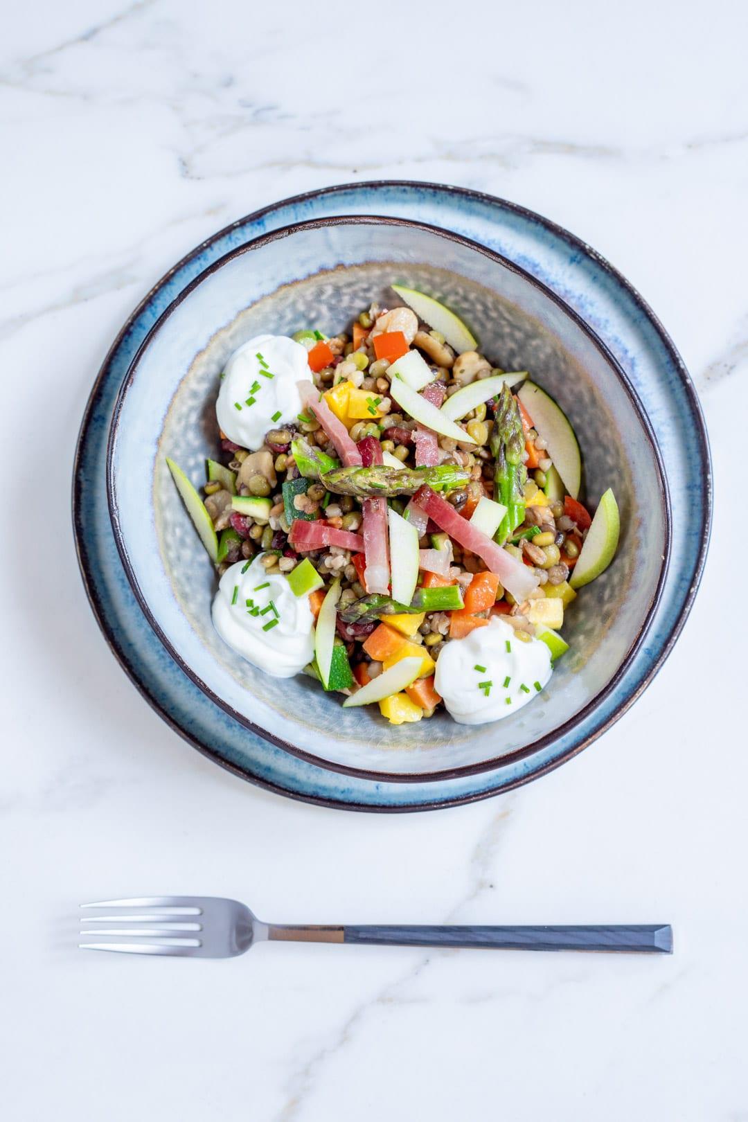Insalata di verdure, cereali, speck e salsa allo skyr pronta per l'assaggio