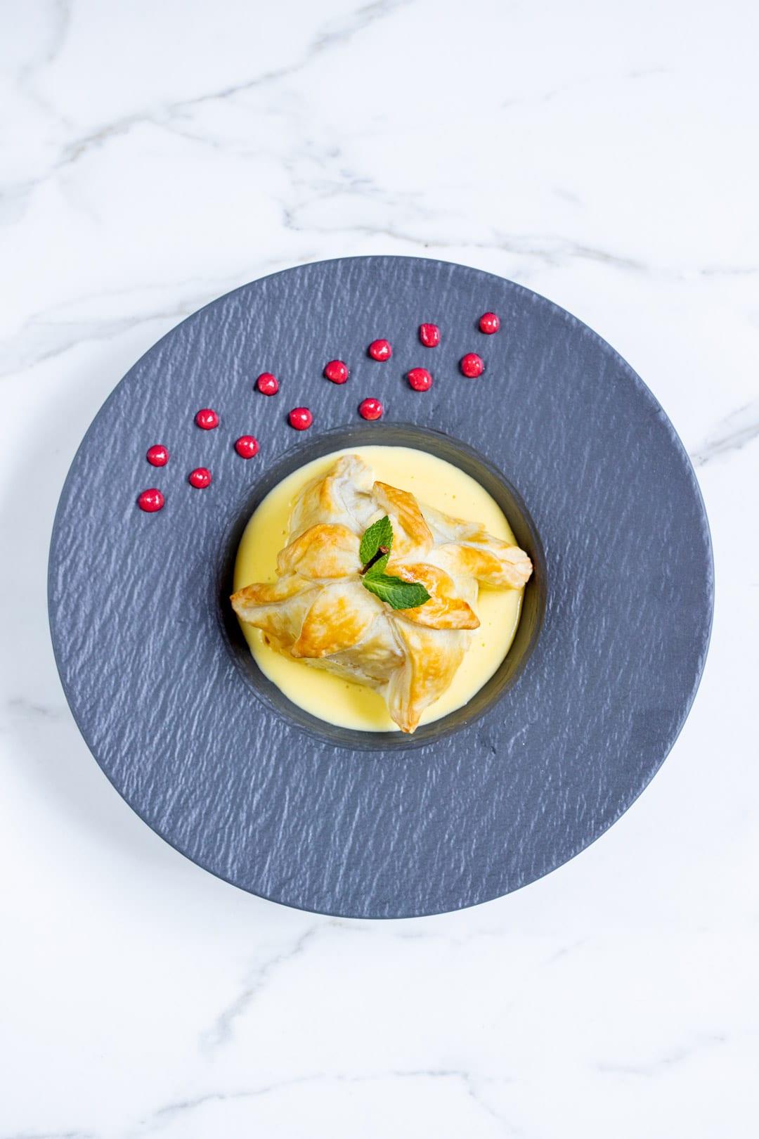 Mela in gabbia con crema inglese e coulis di lamponi pronta nel piatto