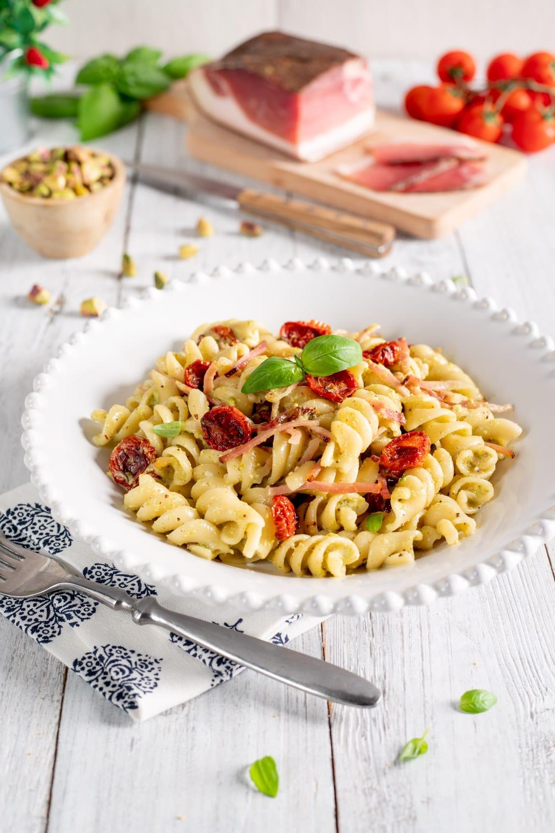 Pasta con pesto di pistacchi, speck e pomodorini confit
