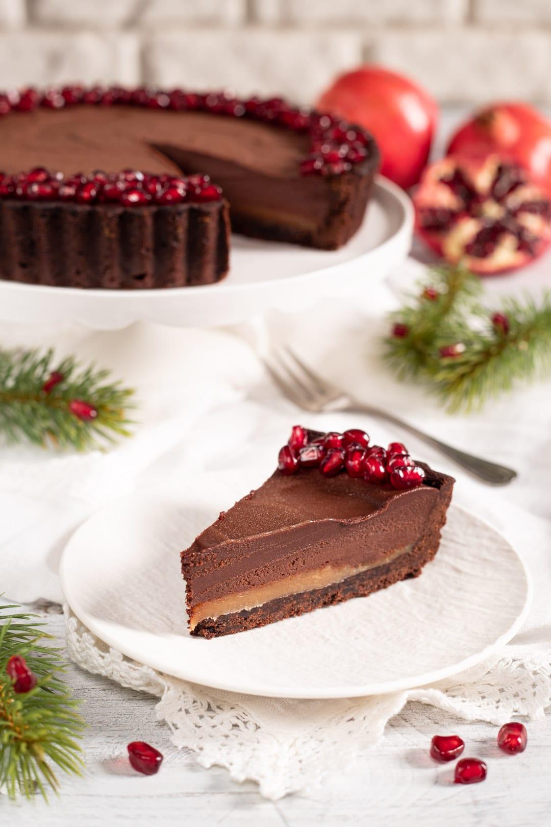 Crostata cioccolata e melagrana con caramello salato fetta pronta da gustare