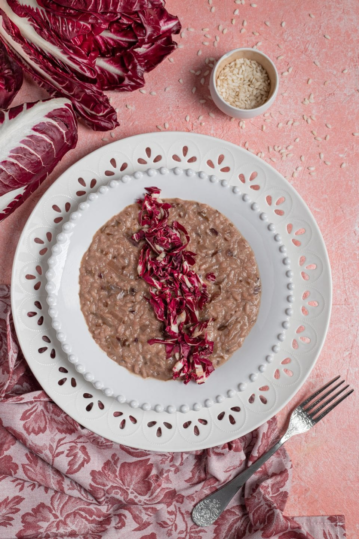 Piatto con risotto e radicchio su tavola.