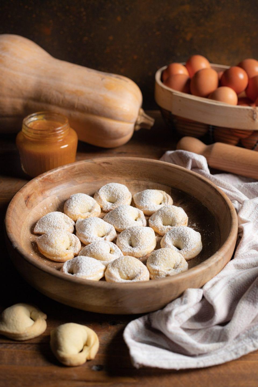 Cappellacci dolci alla zucca su piatto in legno
