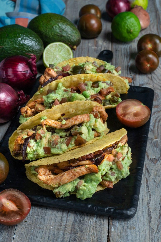 tacos di pollo e guacamole su piatto nero