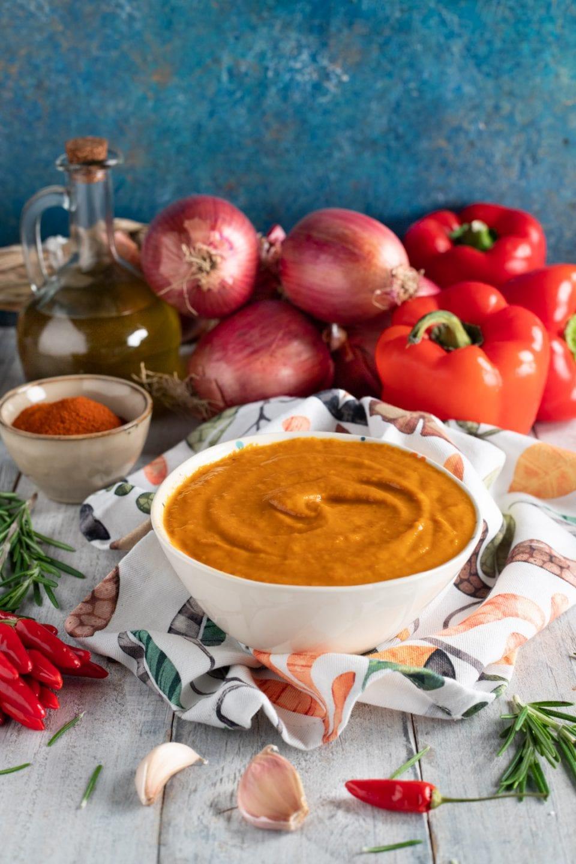 Ciotola con salsa di peperoni e cipolle sullo sfondo